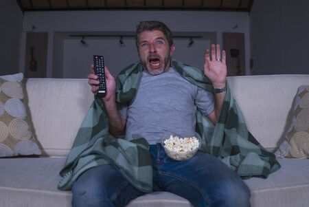 funny home lifestyle portrait of scared and frightened man alone at night in living room couch watching horror scary movie in television screaming and eating popcorn covering with blanket 版權商用圖片 - 127124643