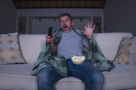 funny home lifestyle portrait of scared and frightened man alone at night in living room couch watching horror scary movie in television screaming and eating popcorn covering with blanket