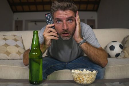 lifestyle portrait of young attractive nervous and excited football supporter man watching soccer game on television at home sofa couch in stress and emotion eating popcorn and drinking beer