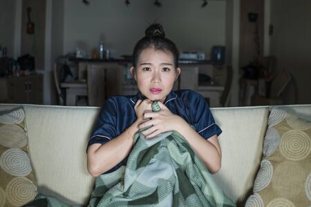 young beautiful happy and cheerful Asian Japanese woman watching TV comedy movie or hilarious show laughing and eating popcorn sitting at home couch with blanket in domestic lifestyle Imagens