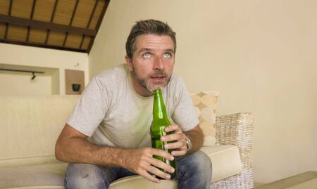 lifestyle portrait of young attractive nervous and excited football supporter man watching soccer game on television at home sofa couch in stress and emotion holding remote and beer bottle Imagens