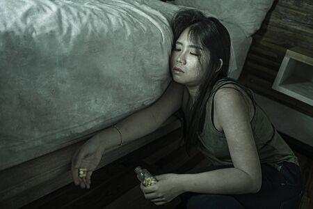 Joven y bella adicta desesperada y desperdiciada Mujer china asiática que toma una sobredosis de drogas en el piso del dormitorio de casa sintiéndose enferma y deprimida sufriendo depresión descomposición en adicción a las pastillas