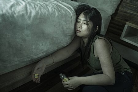 young beautiful desperate and wasted addict Asian Chinese woman taking drug overdose at home bedroom floor feeling sick and depressed suffering depression breakdown in pills addiction