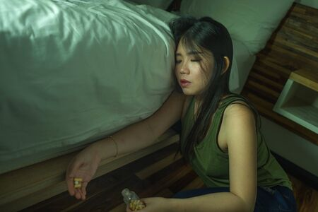 young beautiful desperate and wasted addict Asian Korean woman taking drug overdose at home bedroom floor feeling sick and depressed suffering depression breakdown in pills addiction