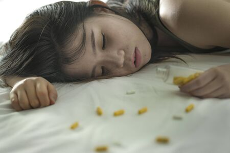 young beautiful desperate and wasted addict Asian Japanese woman taking drug overdose lying on bed feeling sick and depressed suffering depression breakdown passed out in pills addiction