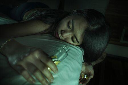 Joven y bella adicta desesperada y desperdiciada Mujer coreana asiática que toma una sobredosis de drogas acostada en la cama sintiéndose enferma y deprimida sufriendo depresión colapso desmayado en adicción a las píldoras