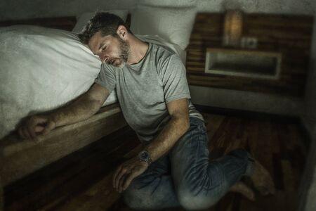 Dramatisches Heimporträt eines jungen verzweifelten und depressiven einsamen Mannes, der auf dem Schlafzimmerboden sitzt und weint, leidet an Angstkrisen und Depressionen und fühlt sich hilflos und verlassen