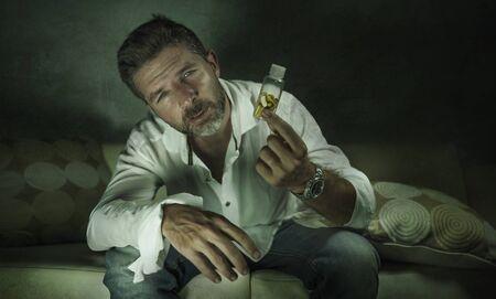 Retrato dramático de un joven adicto a las píldoras deprimido y desperdiciado atractivo que sostiene la botella de tabletas antidepresivas sentado en el sofá en el concepto de adicción a las drogas sobre fondo oscuro y grunge vanguardista Foto de archivo