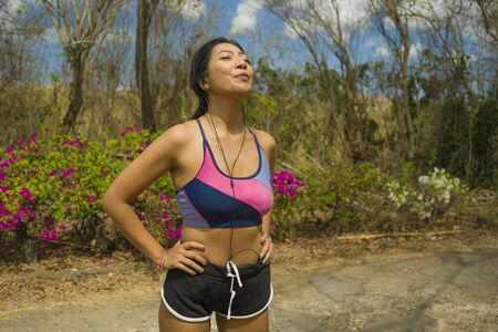 young beautiful tired and breathless runner Asian woman exhausted and sweaty after hard running workout at trail road park in fitness and healthy natural lifestyle concept 写真素材