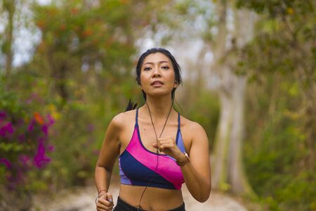 young happy attractive and exotic Asian Indonesian runner woman in jogging workout outdoors at countryside road track nature background running cheerful in healthy lifestyle concept