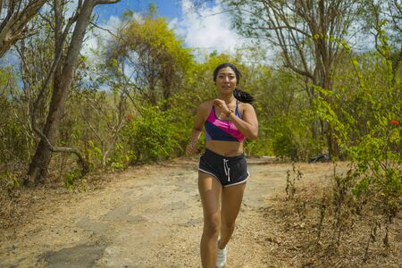 frontal view of young attractive and exotic Asian Indonesian runner woman in jogging workout outdoors at countryside road track nature running sweaty pushing hard in healthy lifestyle concept 写真素材