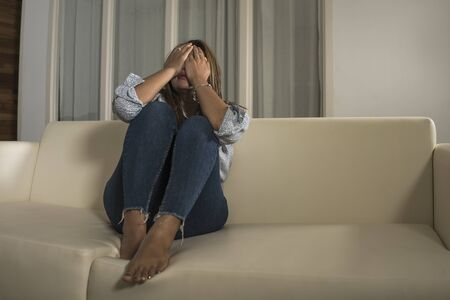 dramatic lifestyle portrait of young sad and depressed girl crying desperate at home couch feeling broken heart suffering depression crisis and anxiety problem covering her face