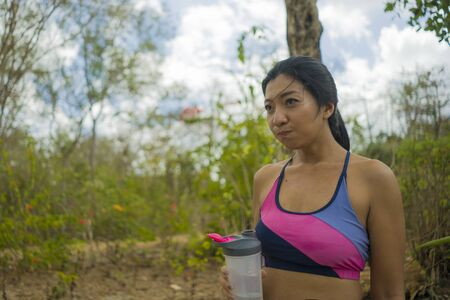 outdoors lifestyle portrait of young attractive tired and thirsty Asian woman drinking water after hard running workout cooling off at beautiful green park in fitness sport and healthy lifestyle conce