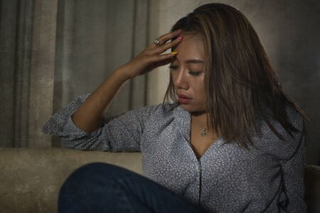 dramatic portrait of young beautiful sad and depressed Asian woman in pain thoughtful and confused at home couch feeling broken heart suffering depression crisis and anxiety problem