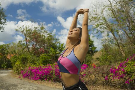 young attractive and healthy runner Asian woman stretching and breathing for cool off or warm up during running workout at beautiful green park in jogging and fitness concept