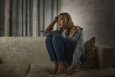 young beautiful sad and depressed Asian woman in pain thoughtful and confused at home couch feeling broken heart suffering depression crisis and anxiety problem 写真素材