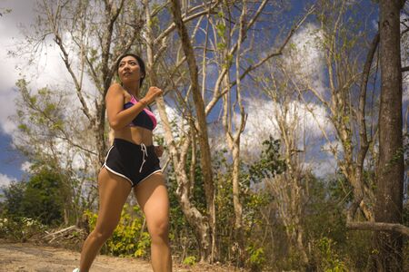 young attractive and exotic Asian Indonesian runner woman in jogging workout outdoors at countryside road track nature running sweaty pushing hard in healthy lifestyle concept