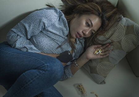 dramatic grunge portrait of young attractive depressed and helpless addict woman feeling desperate sad and lonely abusing pills and tablets suffering depression problem lying on home couch