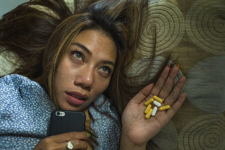 dramatic grunge portrait of young attractive depressed and helpless addict woman feeling desperate sad abusing tablets suffering break up relationship via mobile phone having pills overdose
