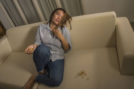 dramatic grunge portrait of young attractive depressed and helpless addict woman feeling desperate sad and lonely abusing pills and tablets suffering depression problem thoughtful on couch