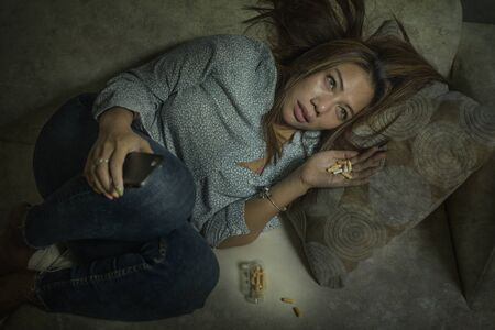 dramatic grunge portrait of young attractive depressed and helpless addict woman feeling desperate sad abusing pills and tablets dumped via mobile phone suffering depression problem