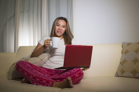 home lifestyle portrait of young attractive and natural hispanic woman in pajamas pants relaxed on couch networking using laptop computer shopping online drinking coffee