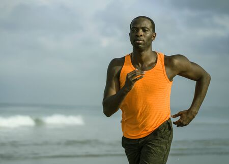young attractive and fit black African American man running on the beach doing Summer fitness jogging workout at the sea in sport exercise and healthy lifestyle concept
