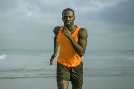 young attractive and fit black afro American man running on the beach doing Summer fitness jogging workout at the sea in sport exercise and healthy lifestyle concept