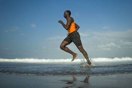 athletic full body portrait of young attractive and fit black afro American man running on the beach doing Summer fitness jogging workout at the sea in sport exercise and healthy lifestyle concept
