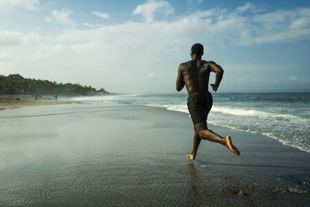 athletic full body portrait of young attractive and fit black African American man running on the beach doing Summer fitness jogging workout at the sea in sport exercise and healthy lifestyle concept Banco de Imagens