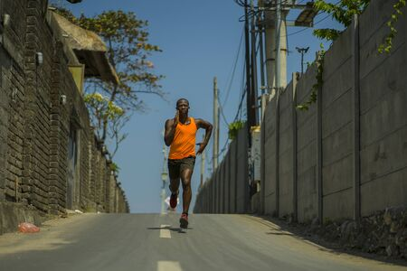 urban runner workout . Young attractive and athletic black African American man running outdoors on asphalt road training hard jogging in sport sacrifice commitment and healthy lifestyle concept Imagens