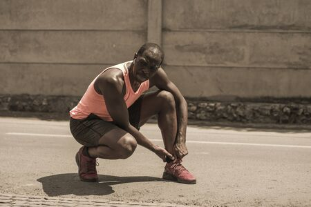 sport injury portrait of young athletic and fit black afro American runner in pain holding his ankle after suffering medical problem with injuried tendon or ligament during urban running workout Stock Photo