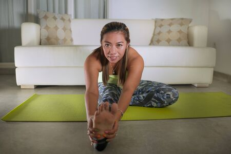 natural home lifestyle portrait of young happy and attractive sweaty Asian Indonesian woman stretching on yoga mat at living room floor doing domestic fitness workout smiling cheerful and relaxed Banco de Imagens