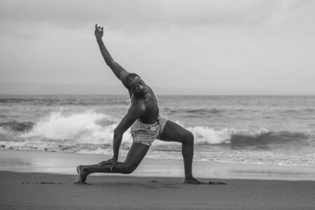 dramatic contemporary dance choreographer doing ballet beach workout . young attractive and athletic afro black American man dancing on sunrise doing performance rehearsal