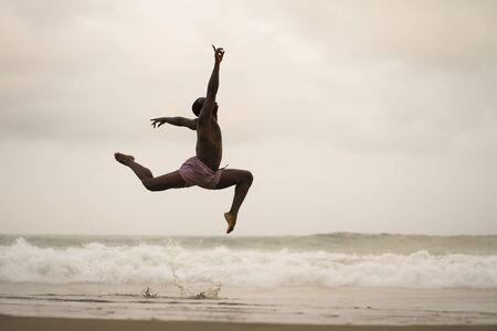 dramatic contemporary dance choreographer doing ballet beach workout . young attractive and athletic afro black American man dancing on sunrise jumping doing performance rehearsal