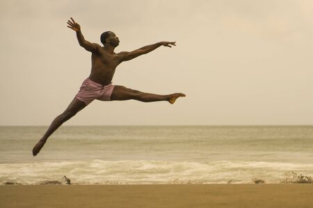 dramatic contemporary dance choreographer doing ballet beach workout . young attractive and athletic black African American man dancing on sunrise jumping elegant and with amazing plasticity