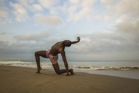 contemporary dance choreographer and dancer doing ballet beach workout . a young attractive and athletic black African American man dancing on sunrise doing dramatic performance
