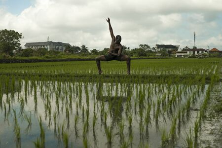 artistic dramatic outdoors portrait of young attractive contemporary ballet dancer and choreographer , a black afro American man dancing and posing on tropical rice field background