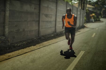 runner lifestyle portrait of young attractive and fit black afro American professional sport man with athletic body running on city street pushing hard under harsh sun in urban background 写真素材