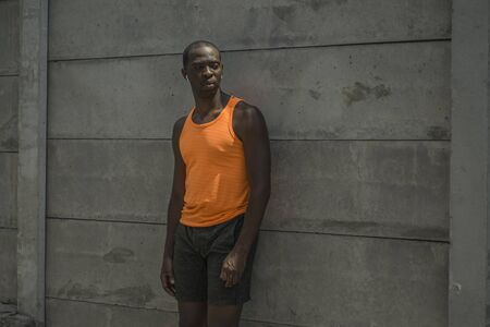 urban runner lifestyle portrait of young attractive and athletic black afro American sport man posing cool in badass style on street wall after running workout 写真素材