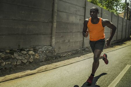 runner lifestyle portrait of young attractive and fit black African American professional sport man with athletic body running on city street pushing hard under harsh sun in urban background 写真素材