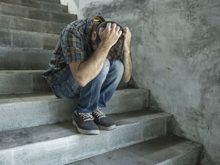 dramatic lifestyle portrait of young depressed and sad man sitting alone outdoors on dark street staircase suffering depression problem and anxiety crisis crying desperate feeling miserable 스톡 콘텐츠