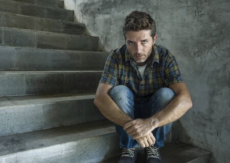 dramatic lifestyle portrait of young depressed and sad man sitting alone outdoors on dark street staircase suffering depression problem looking worried thinking and feeling miserable