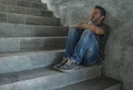 dramatic portrait of young depressed and desperate man sitting outdoors on dark grunge street corner staircase feeling sick suffering depression problem and anxiety crisis in mental health concept Stock Photo