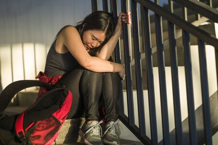 Dramatic portrait of Asian female college student bullied. Young depressed and sad Chinese girl sitting lonely on campus staircase suffering bullying and harassment feeling desperate and excluded Stock fotó
