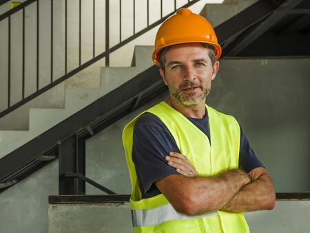 blue collar construction worker. Corporate portrait of young attractive and happy builder man or constructor posing confident smiling wearing building helmet and vest in blue collar job lifestyle