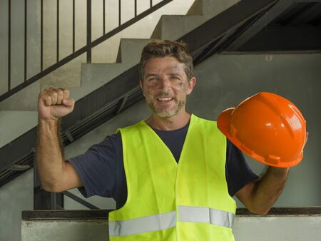 Satisfied blue collar construction worker. Natural portrait of young attractive and happy builder man or constructor posing cheerful smiling in blue collar job lifestyle and work success Banque d'images