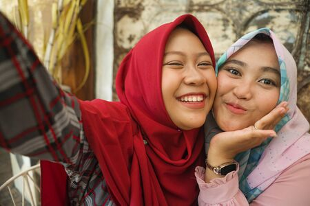 Muslim teenager student girlfriends selfie. Happy and pretty Asian Indonesian girls in traditional Islamic hijab head scarf taking selfie together having fun at cafe in friendship and social media concept Stock Photo