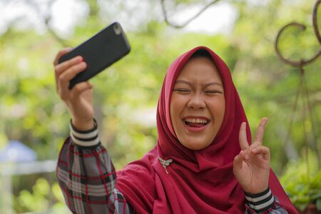 young beautiful happy and cheerful Asian Indonesia student girl wearing Islam traditional hijab head scarf taking selfie with mobile phone for internet social media in Muslim student lifestyle concept