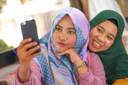 Muslim teenager student girlfriends selfie. Happy and pretty Asian Indonesian girls in traditional Islamic hijab head scarf taking selfie together having fun in friendship and social media concept
